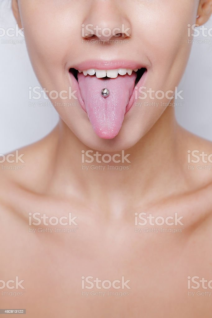 Beautiful woman sticking out her tongue and showing young piercing stock photo