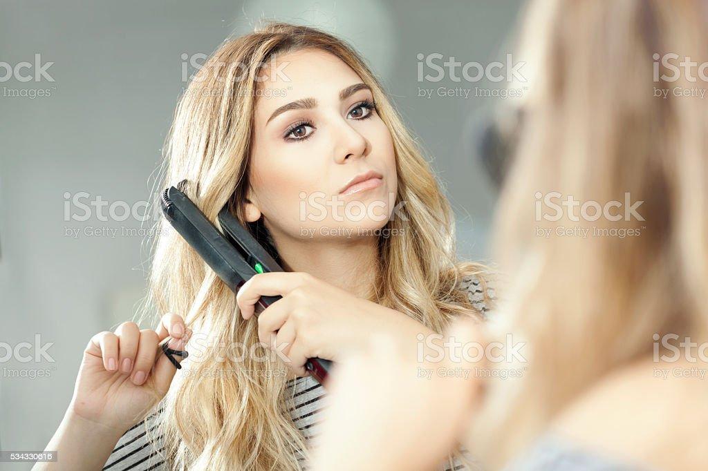 Beautiful woman straightening her hair stock photo