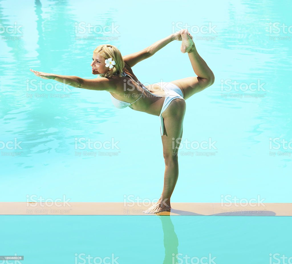 Beautiful woman stretching on the edge of swimming pool. royalty-free stock photo
