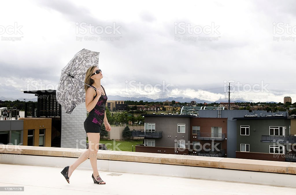 Beautiful Woman Strolls on Rooftop With Umbrella stock photo