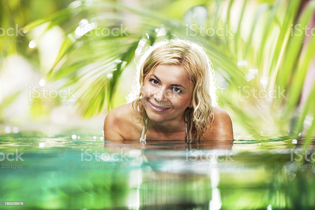 Beautiful woman swimming in the tropical pool. royalty-free stock photo