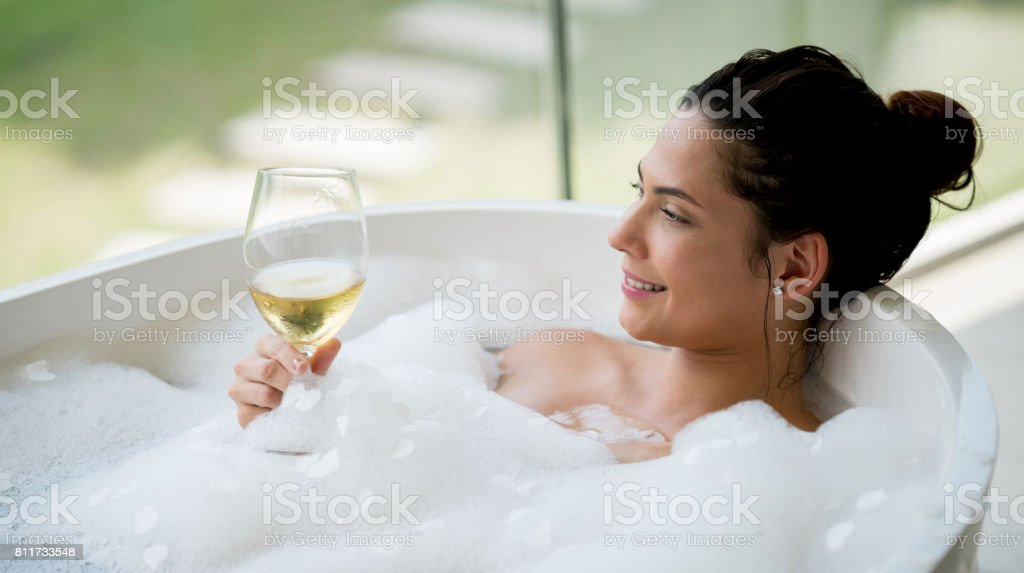 Beautiful woman taking a bath and drinking a glass of wine stock photo