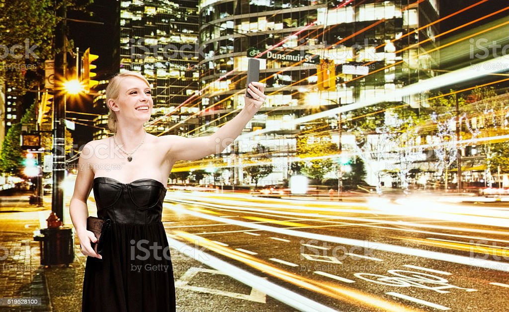 Beautiful woman taking a selfie outdoor at night stock photo