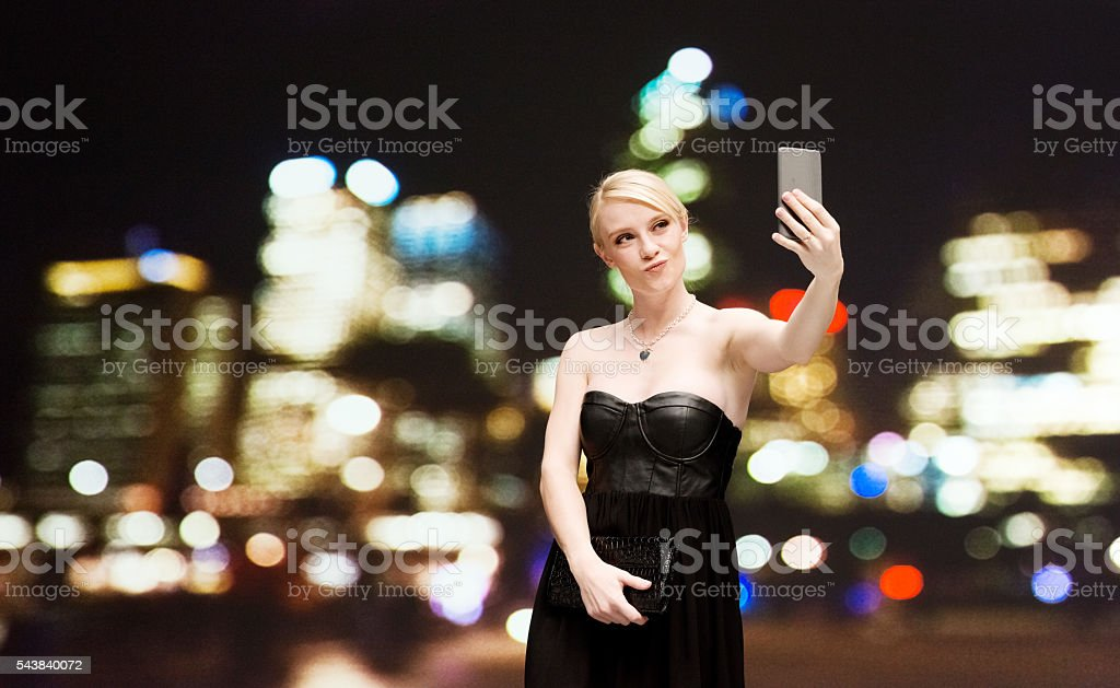 Beautiful woman taking a selfie outdoors stock photo