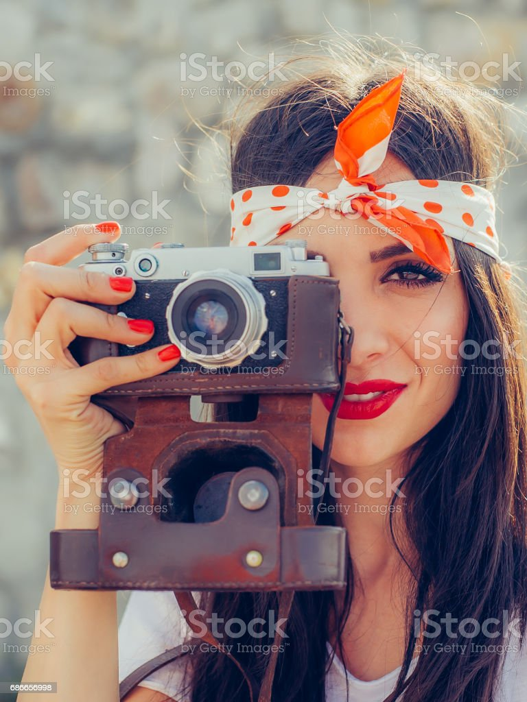 Beautiful woman taking photo with old fashioned film camera stock photo