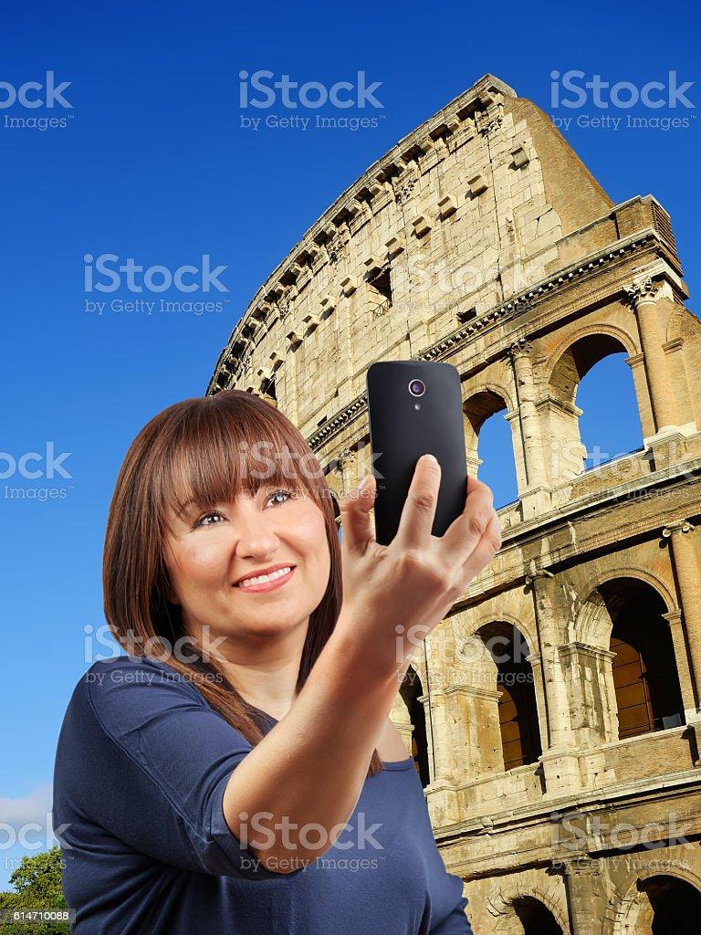 Beautiful woman taking selfie Colosseum Rome stock photo