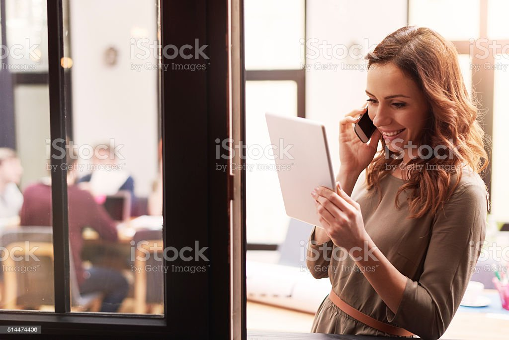 Beautiful woman talking by mobile phone at the office stock photo