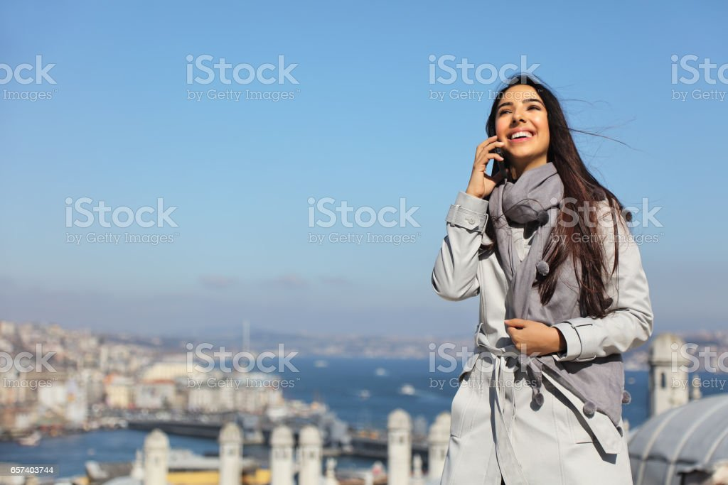 Beautiful woman talking on cell phone at the Suleymaniye Mosque enjoying the amazing view of Istanbul, Turkey stock photo