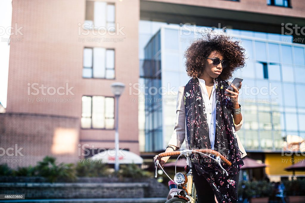 Beautiful woman talking on the phone with the bike stock photo