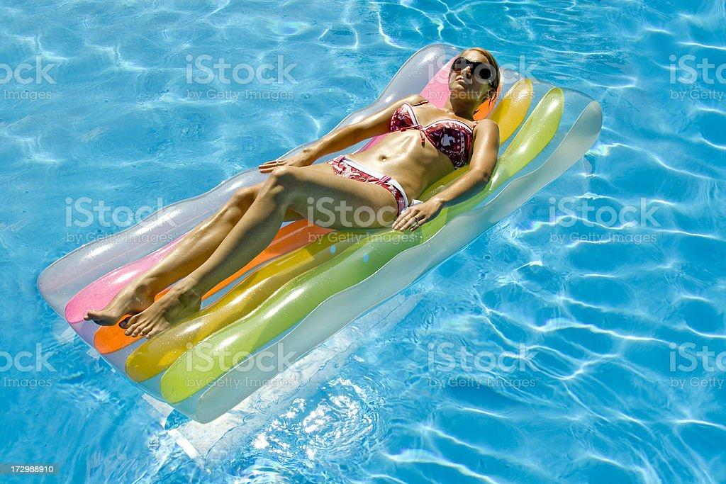 Beautiful woman tanning on air mattress royalty-free stock photo