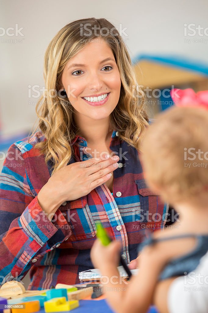 Beautiful woman teaching preschooler sign language stock photo