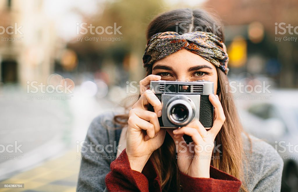 Beautiful woman teasing with a retro camera. stock photo