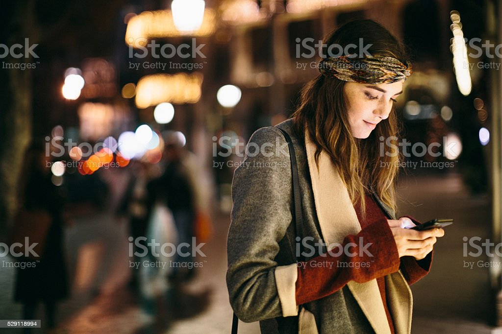 Beautiful woman texting at night in Barcelona. stock photo