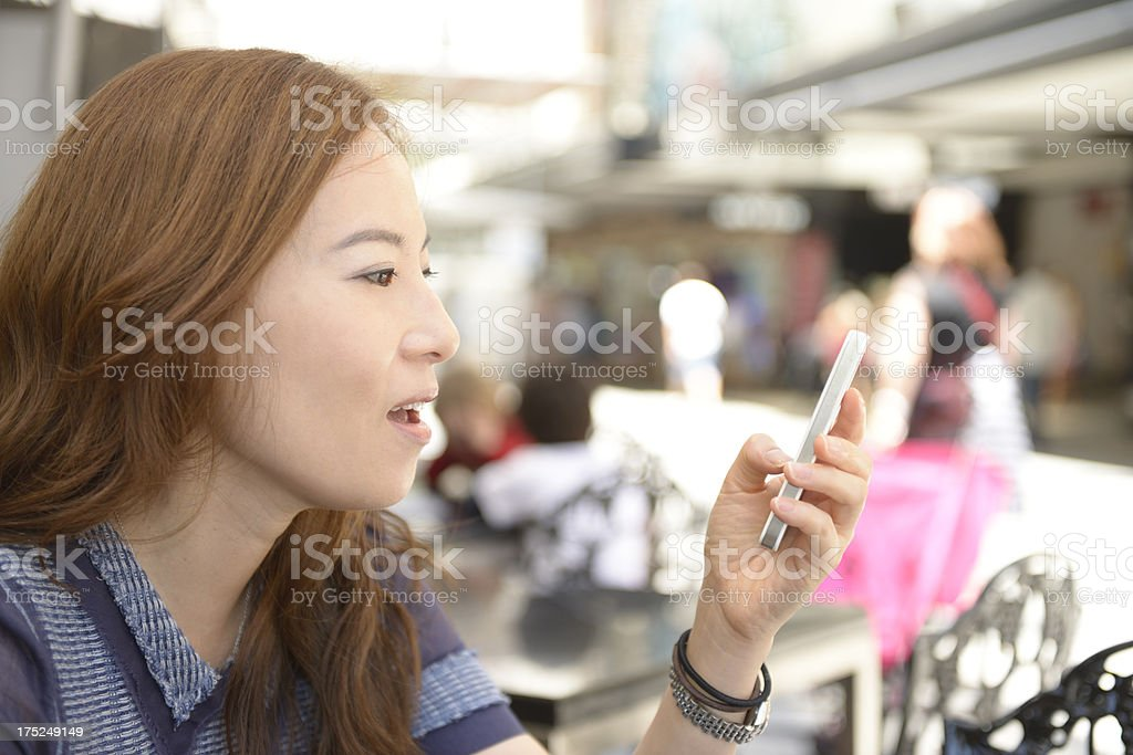 Beautiful woman textmessaging with smart phone in an outdoor caf stock photo