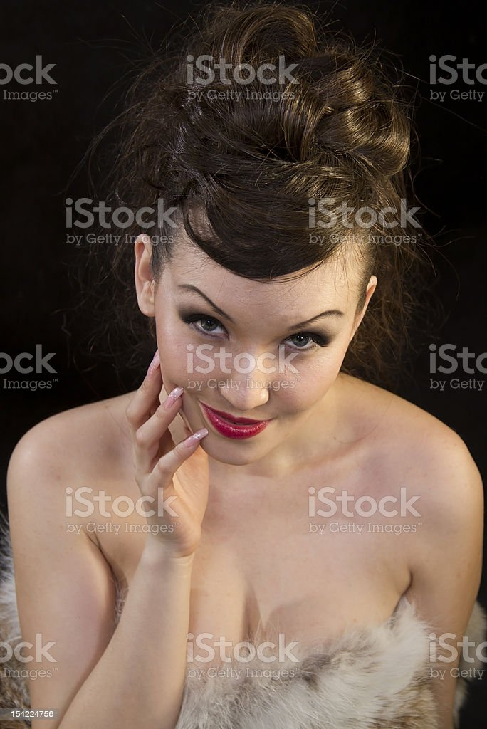 Beautiful woman touching face dressed fur on black stock photo