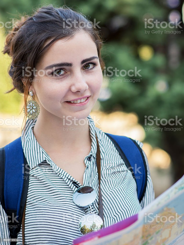 Beautiful woman traveler holding location map in hands stock photo