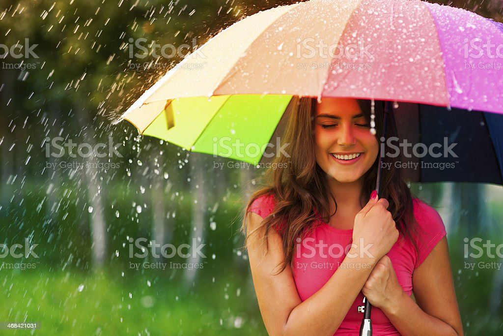Beautiful woman under rainbow umbrella stock photo