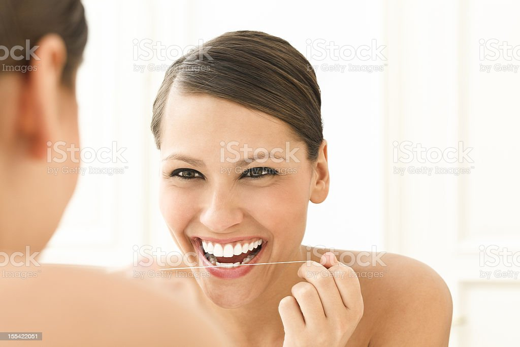 Beautiful woman using dental floss stock photo