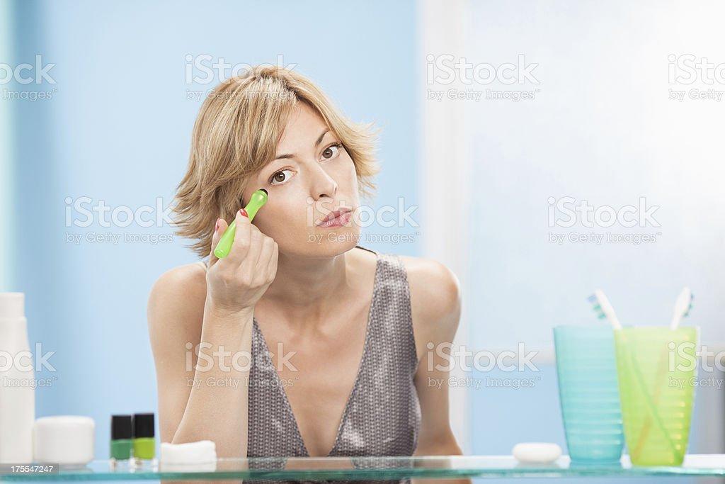 Beautiful woman using eye roller stock photo