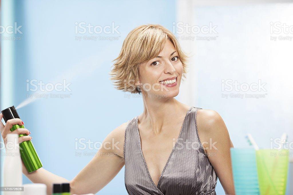Beautiful woman using hair spray stock photo