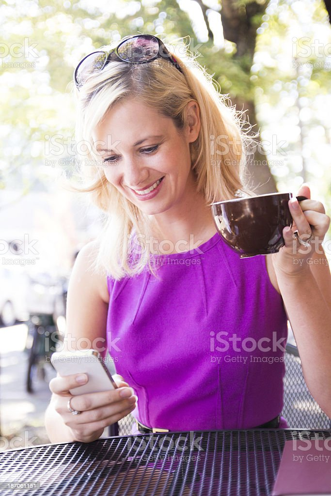 Beautiful woman using her smart phone at an outdoor cafe royalty-free stock photo