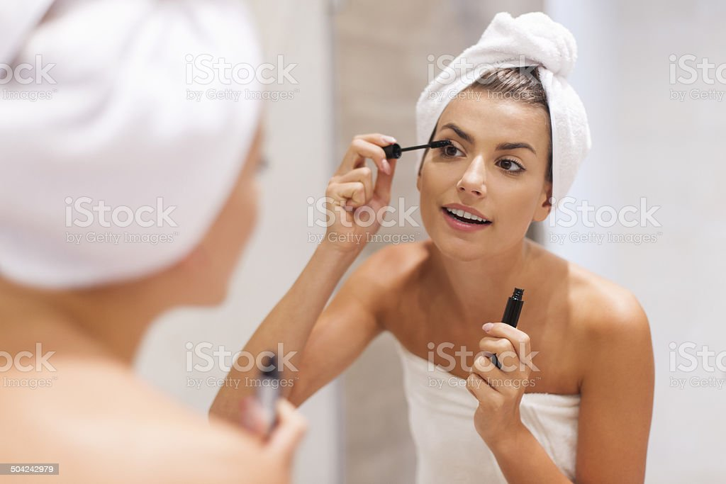Beautiful woman using mascara in bathroom stock photo