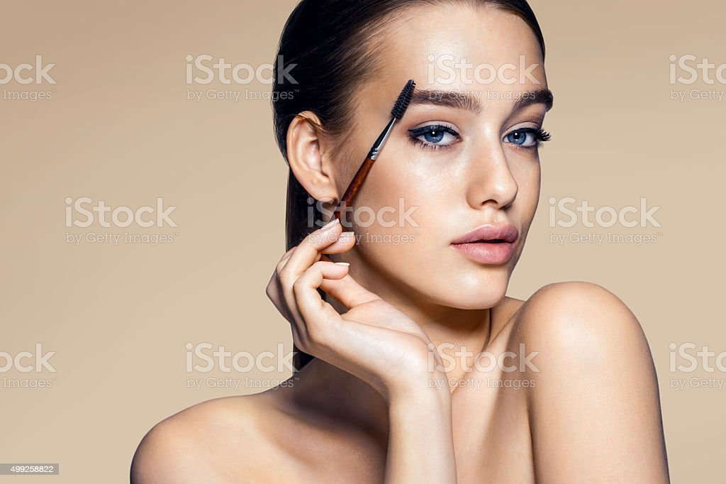 Beautiful woman using mascara stock photo