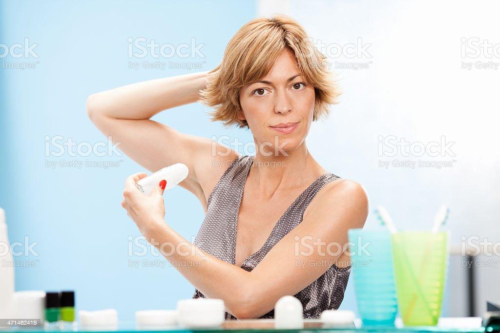 Beautiful woman using roll on deodorant stock photo