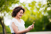 Beautiful woman using smart phone in the park