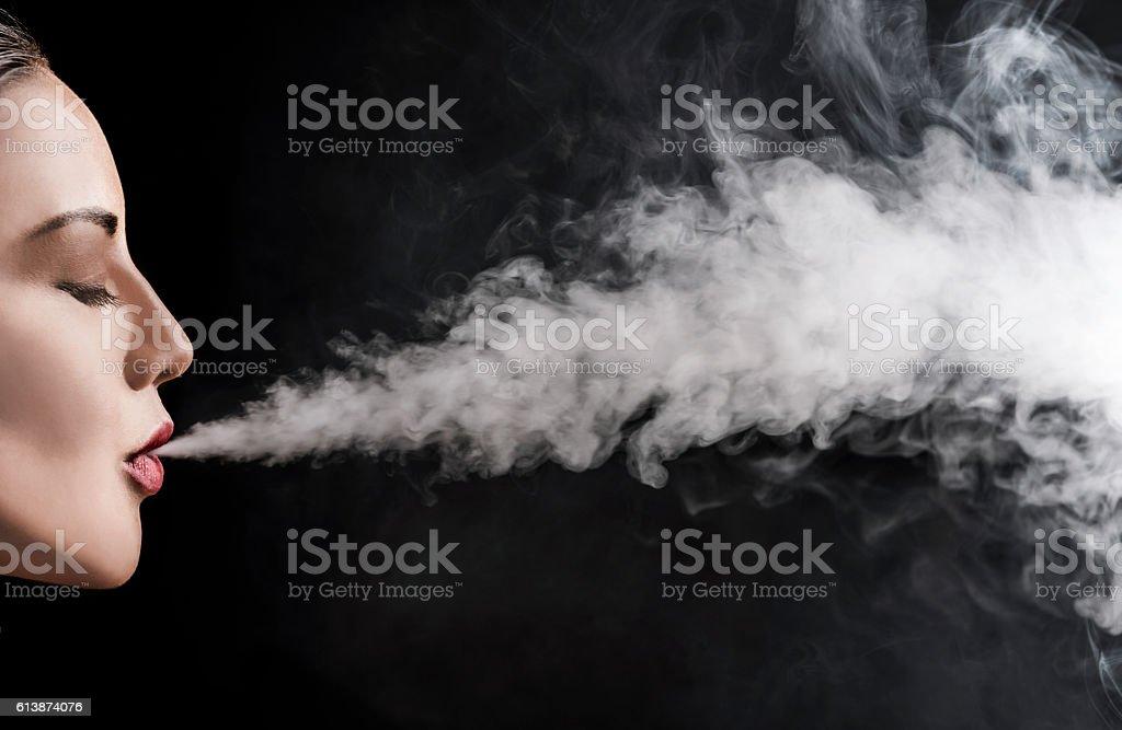Beautiful woman vaping with smoke stock photo
