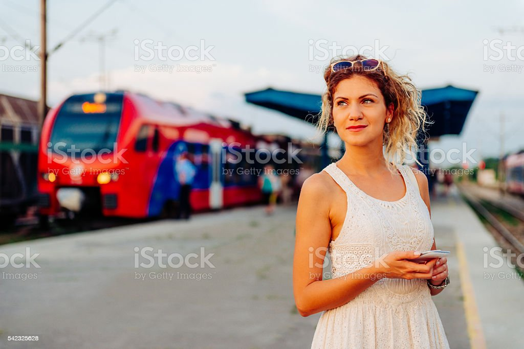 Beautiful woman waiting for train on railway station stock photo