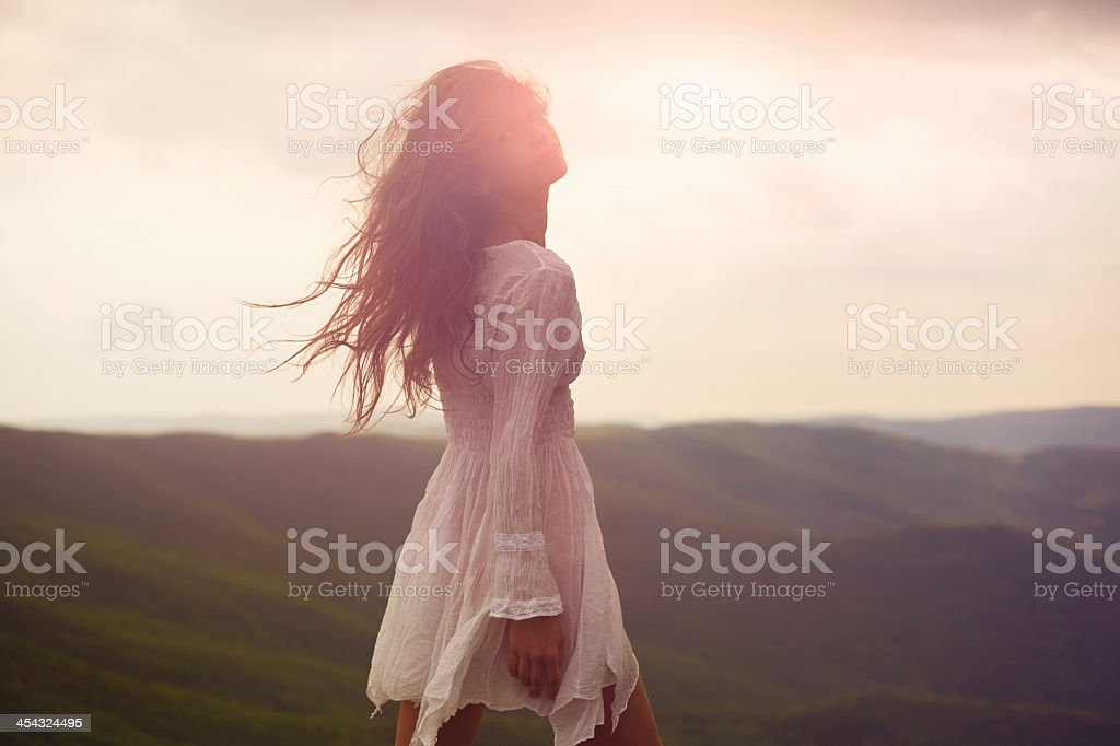A beautiful woman walking around a mountainside stock photo