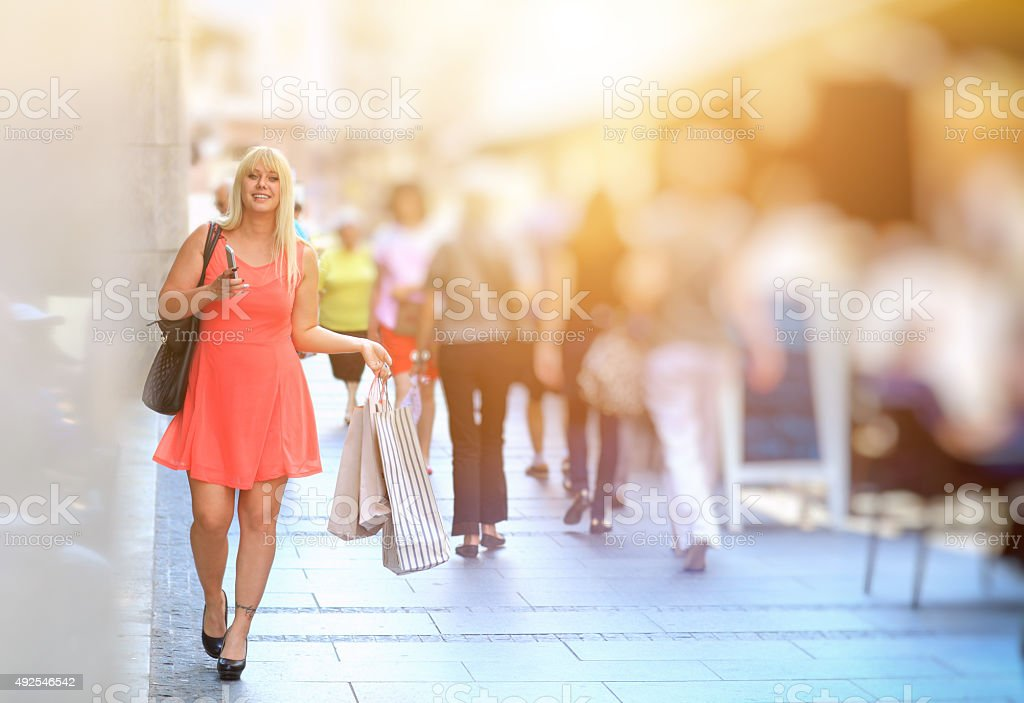 Beautiful woman walking down the street with shopping bags stock photo