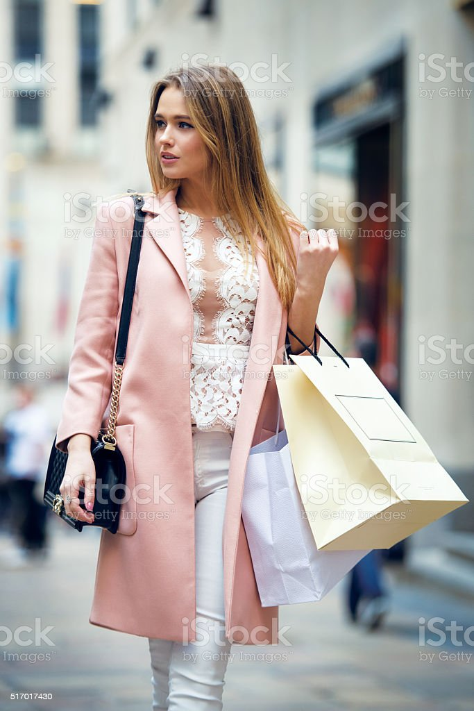 Beautiful woman walking on city street with bags after shopping stock photo