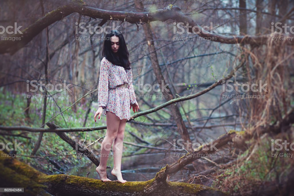 Beautiful woman walking on log in forest. stock photo
