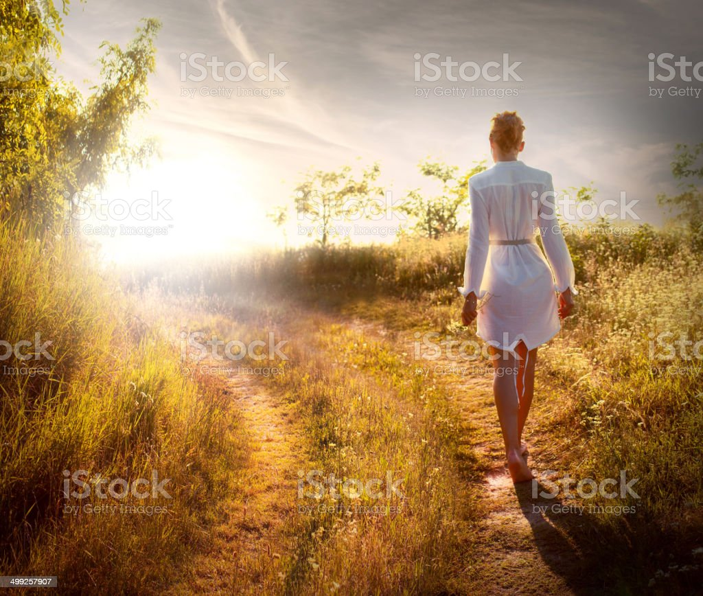 Beautiful woman walking on the field stock photo