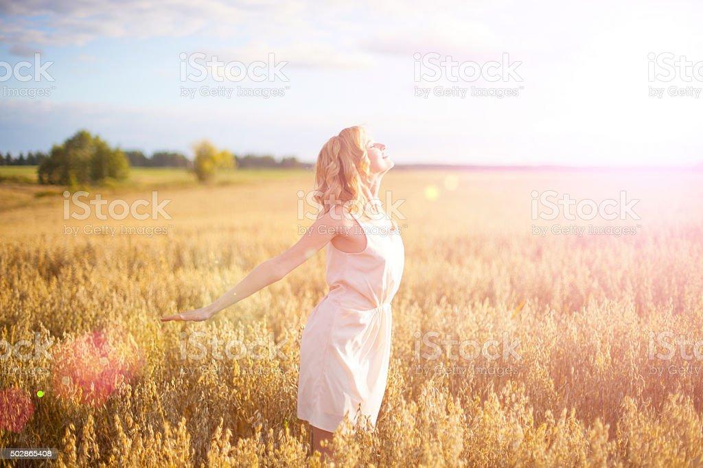 Beautiful woman walking on wheat field stock photo