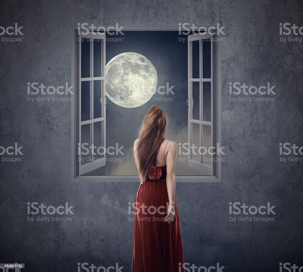 Beautiful woman walking to opened window with moon stock photo