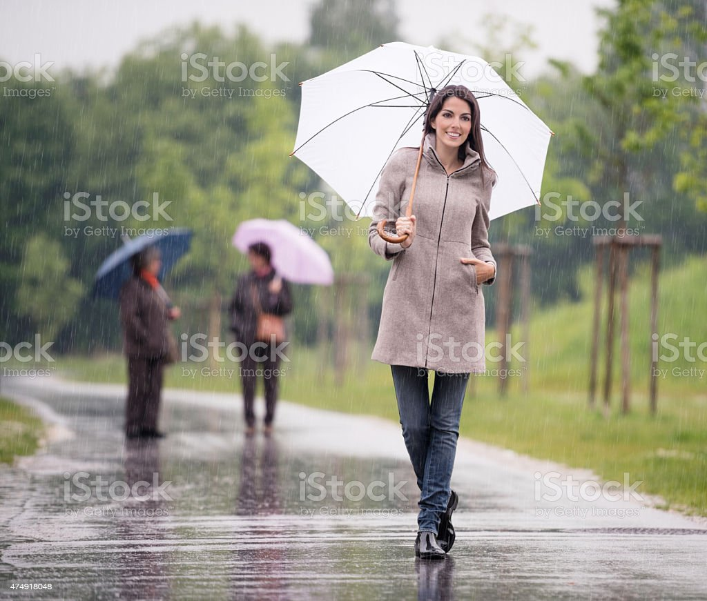 Beautiful Woman walking under her Umbrella in the Rain stock photo