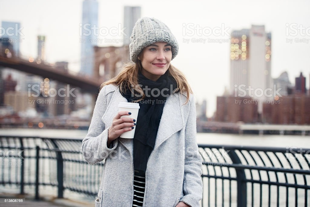 Beautiful woman walking with coffee cup in New York City stock photo
