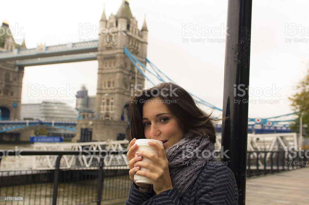 Beautiful woman warms up drinking from a coffee cup stock photo