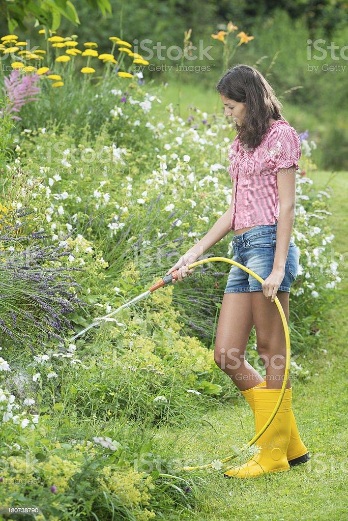 Beautiful Woman watering the Flower Garden stock photo