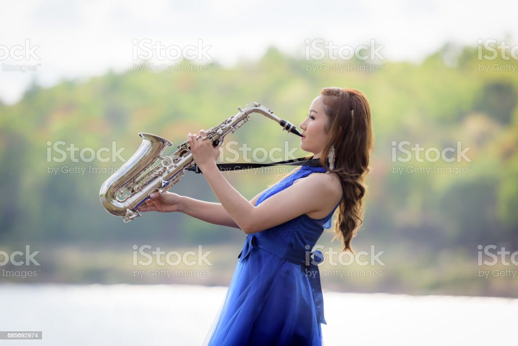 Beautiful woman wear blue evening dress sound saxophone over mountains and rivers background. stock photo