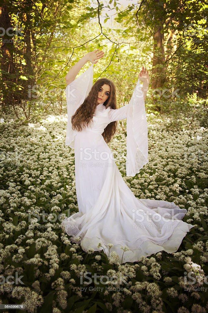 Beautiful woman wearing a long white dress dancing stock photo