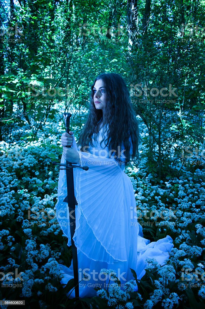 Beautiful woman wearing a long white dress holding a sword stock photo