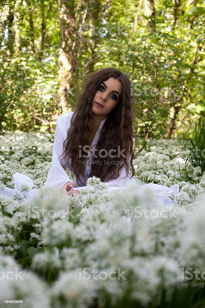 Beautiful woman wearing a white dress sitting in a forest stock photo