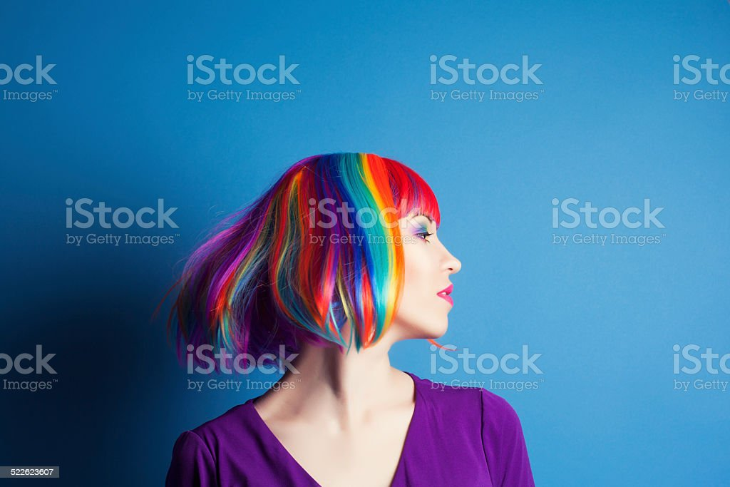 beautiful woman wearing colorful wig against blue background stock photo