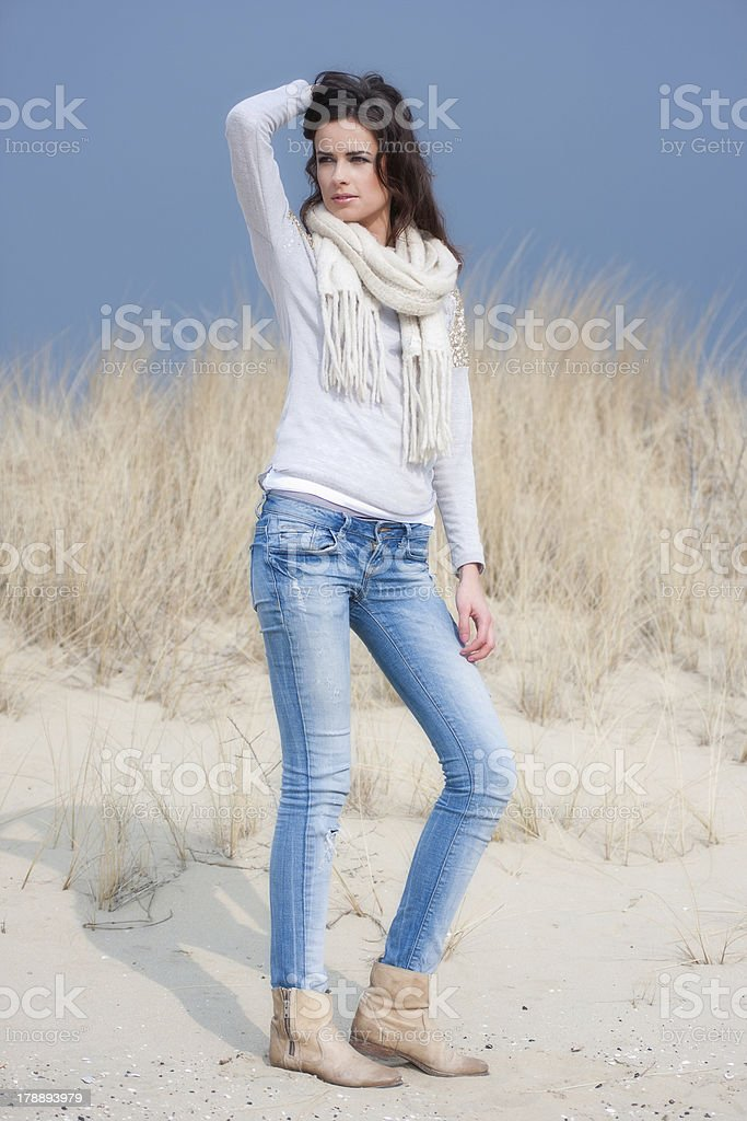 Beautiful woman wearing grey shirt and jeans in the dunes royalty-free stock photo