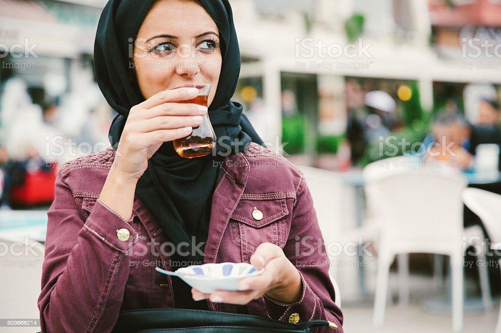 Beautiful Woman Wearing Headscarf Drinking Turkish Tea In A Cafè stock photo
