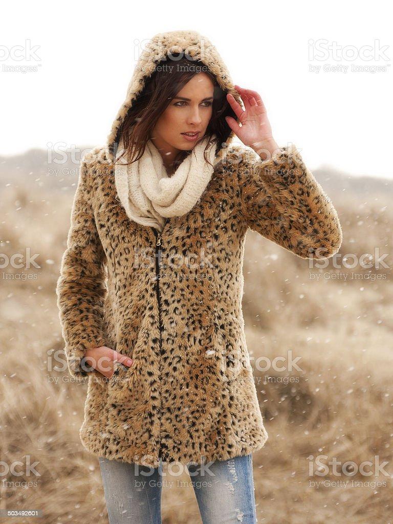 Beautiful woman wearing tigerprint coat in snow royalty-free stock photo